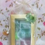 ชุดของขวัญขนาดเล็กบรรจุในกล่องสีทองในถุงผ้าไหมแก้วสีครีม